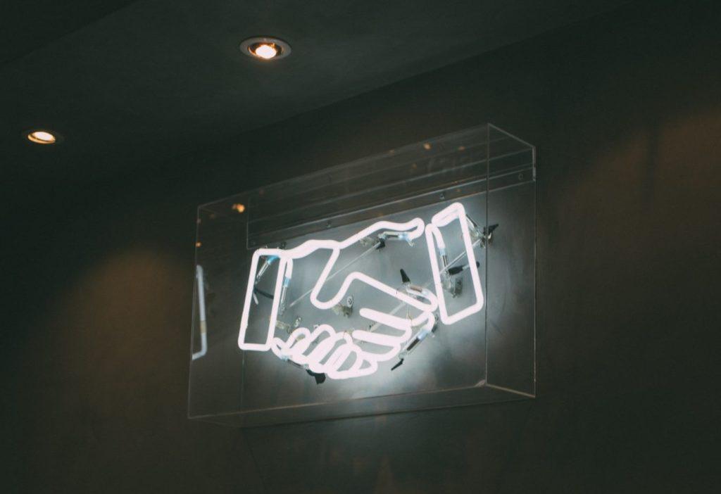 neon sign of a handshake