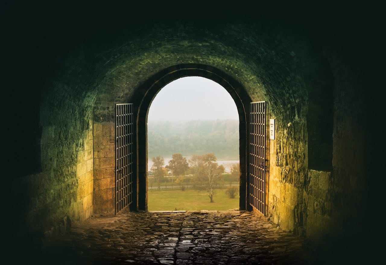 Looking out of a tunnel with an open gate