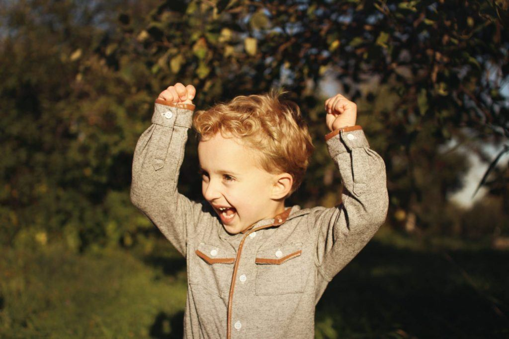 Child smiling and raising their arms above their head with excitement